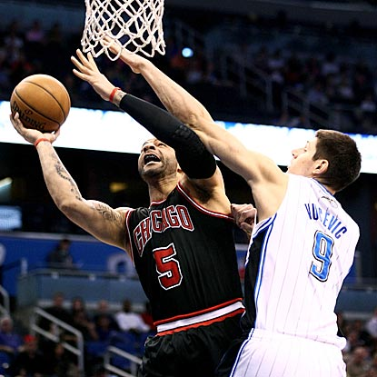 Carlos Boozer attempts to get off a shot against Orlando's Nikola Vucevic during the first quarter. (US Presswire)