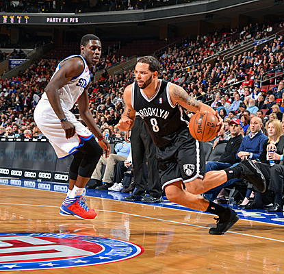Deron Williams, who scores 22 points for Brooklyn, drives against Philadelphia's Jrue Holiday in the Nets' win. (Getty Images)