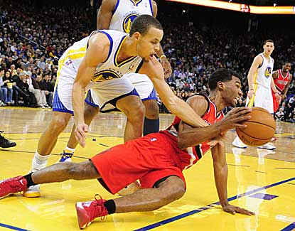 Golden State's Stephen Curry, who finishes with 22 points, battles with Portland's Ronnie Price for a loose ball.  (US Presswire)