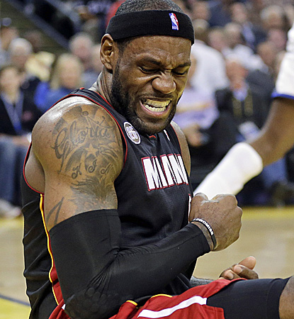 The Heat get a scare when LeBron James falls down after taking a shot against the Warriors during the first half. (AP)