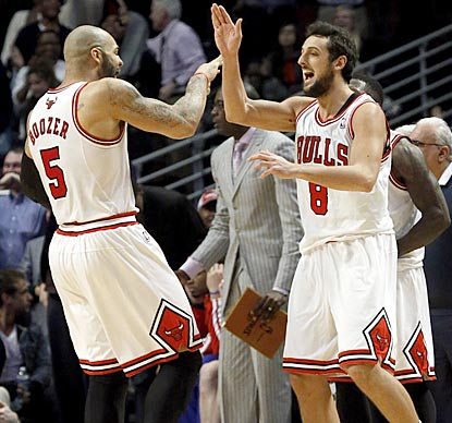 Carlos Boozer (left) is among the first to congratulate Marco Belinelli for making what proves to be the winning shot.  (AP)