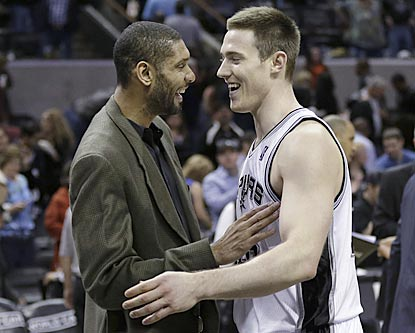 Tim Duncan congratulates Aron Baynes on his seven-point, nine-board effort during his first significant NBA playing time.  (AP)