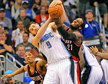 Orlando's Nikola Vucevic (left), who scores 17 points and adds 19 rebounds, battles with J.J. Hickson for the ball. (US Presswire)