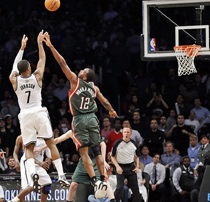 After draining a 3 that forces overtime, the Nets' Joe Johnson sinks the game-winning shot before the buzzer sounds. (AP)