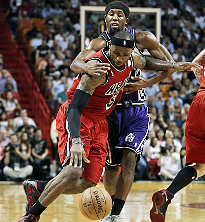 Miami's LeBron James, who scores 40 points and registers a career-high 16 assists, is fouled by Sacramento's John Salmons. (AP)