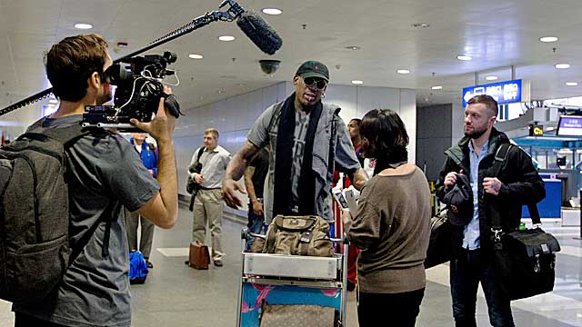 TV crews surround Rodman before he departs Beijing on Tuesday for North Korea. (AP)