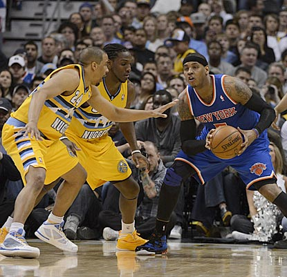A balky knee slows down Carmelo Anthony, as well as defense from Denver's Andre Miller and Kenneth Faried.  (Getty Images)