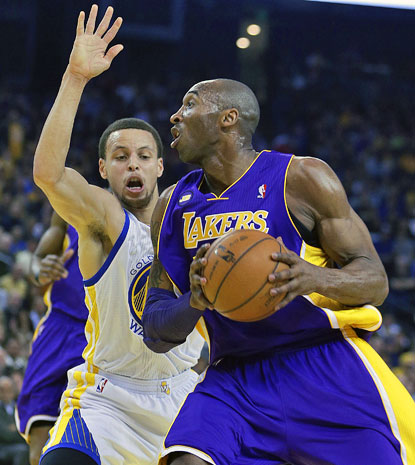 Stephen Curry, who scores 25 points and tallies 10 assists, defends Kobe Bryant. Bryant finishes with 36 points. (AP)