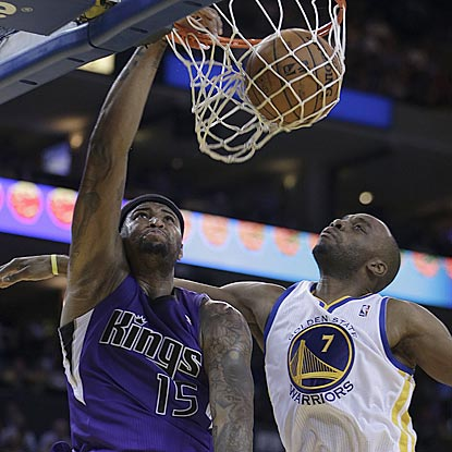 Sacramento's DeMarcus Cousins drives past Golden State's Carl Landry and dunks during the second half.  (AP)
