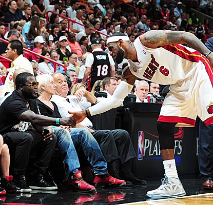 LeBron James takes time out from scoring 24 points for the Heat to greet a fan courtside in Miami. (Getty Images)