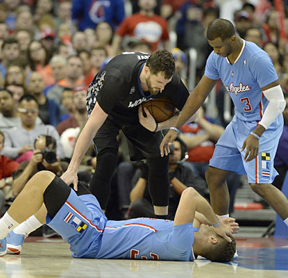 Kevin Love and Chris Paul check on Blake Griffin, who takes a hard shot to the head but is able to shake it off. (USATSI)