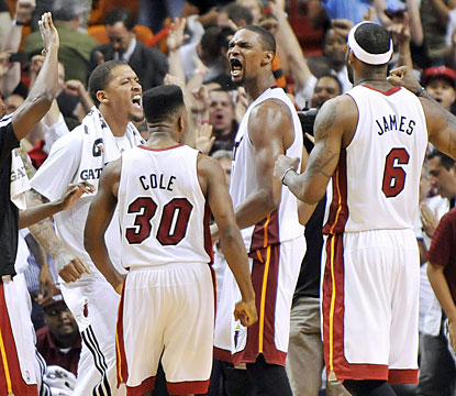 The Heat surround Chris Bosh, who blocks Damian Lillard's layup in the final seconds to preserve the win. (USATSI)