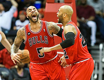 A rather animated Carlos Boozer (left) celebrates his dunk during the second half with Taj Gibson.  (USATSI)