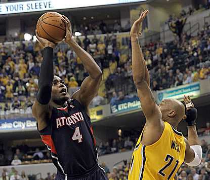 Paul Millsap, shown shooting over David West, records a double-double in Atlanta's shockingly easy victory at Indiana.  (USATSI)