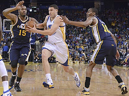 Golden State's Klay Thompson drives between Utah's Derrick Favors and Alec Burks during the second quarter.  (USATSI)