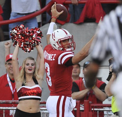 Taylor Martinez (266 total yards, three TDs) becomes the first Husker quarterback to run for more than 100 yards in a game.  (AP)
