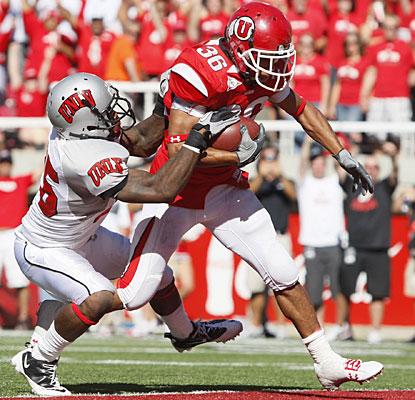 Despite a defender's best effort, Eddie Wide runs in for one of his two touchdowns.  (AP)
