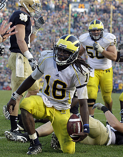 QB Denard Robinson, who compiles 502 total yards and three scores against ND, gets up after providing the winning touchdown.   (AP)