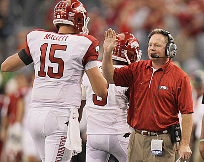 Arkansas coach Bobby Petrino (right) congratulates QB Ryan Mallett after a first-half touchdown.  (AP)