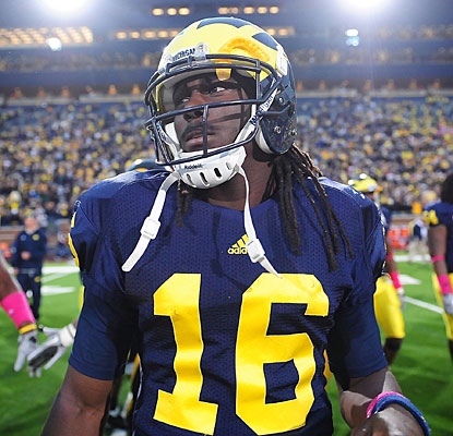 Denard Robinson walks off the field after Michigan's loss, which he left early because of an arm injury.  (US Presswire)