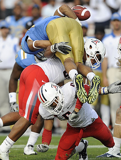 UCLA's Taylor Embree loses the ball upon being hammered by R.J. Young and Shaquille Richardson.  (AP)