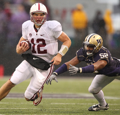 Stanford QB Andrew Luck (12) runs all over Hau'oli Jamora (52) and the Huskies during a dominant shutout victory.   (Getty Images)
