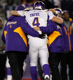 Favre is helped off the field after suffering a chin-splitting hit. (US Presswire)