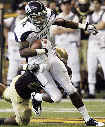 Nevada receiver Brandon Wimberly breaks a tackle by Idaho linebacker Tre'Shawn Robinson.  (AP)