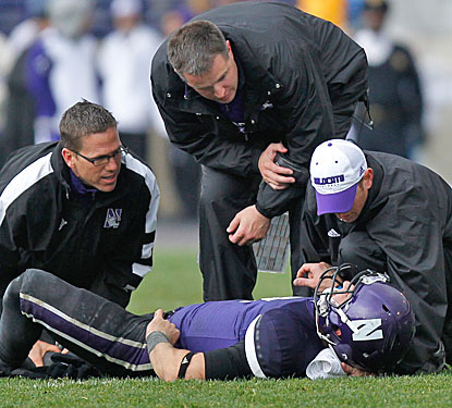 Northwestern coach Pat Fitzgerald checks on Dan Persa, who suffers a season-ending injury after throwing the go-ahead TD.  (US Presswire)