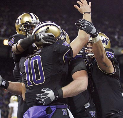 The Huskies mob Jake Locker after he scores with Washington wearing all black for the first time in school history.  (US Presswire)