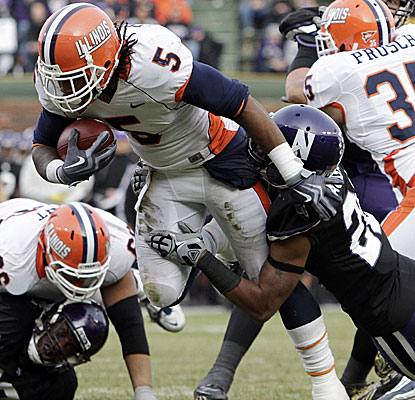 Northwestern's Justan Vaughn tries to contain Illinois' Mikel Leshoure but the running back ends up with 330 yards. (AP)