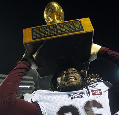 Pernell McPhee hoists up the Golden Egg trophy after his Bulldogs dominate the Rebels for most of the game.  (AP)