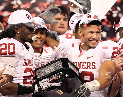 After an exceptional performance on defense, Travis Lewis (28) is more than worthy of holding the Big 12 championship trophy.  (US Presswire)
