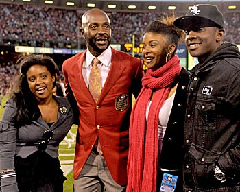 Jerry Rice Jr. (right) strikes a family pose last September as his dad's famed No. 80 jersey is retired at Candlestick Park. (US Presswire)