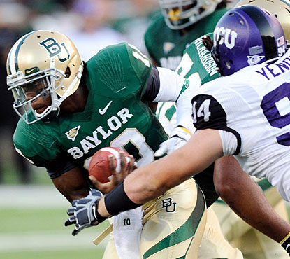 Robert Griffin, who connects for five touchdowns, avoids a rush by TCU defensive tackle D.J. Yendrey. (US Presswire)