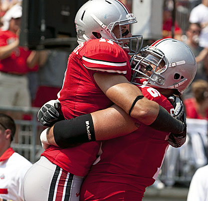 TE Jake Stoneburner gets a hug from OL J.B. Shugarts after the second of his three TDs in Ohio State's win. (US Presswire)