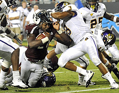 South Carolina's Marcus Lattimore gets his helmet ripped off while trying to bull his way forward for extra yards. (US Presswire)