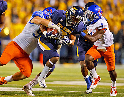 Toledo's Eric Page (center) is tackled by Boise State's Byron Hout (left) and Jerrell Gavins in Toledo. (AP)