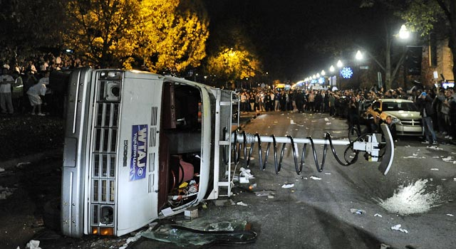 A news van is tipped over as Penn State fans mob the campus Wednesday night. (Getty Images)