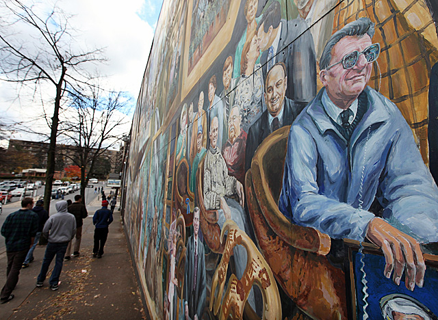 PSU students walk past a mural entitled 'Inspiration,' which depicts ex-coach Joe Paterno. (Getty Images)