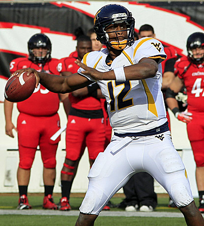 Geno Smith, who throws for 372 yards and a score, leads WVU on a game-clinching drive to knock off No. 23 Cincinnati. (AP)