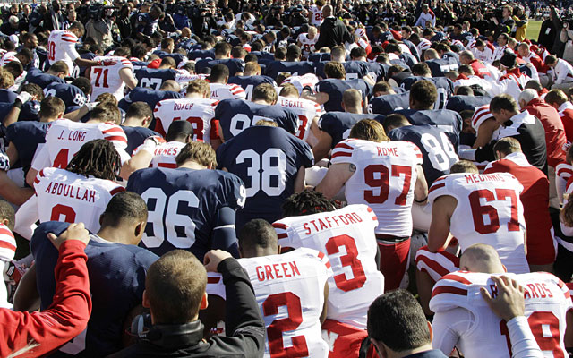 Penn State and Nebraska players join for a pregame prayer that helps justify playing the game. (AP)