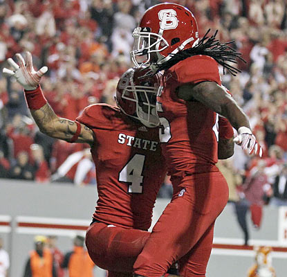 Tobias Palmer (4) celebrates his 43-yard touchdown catch with teammates. The Wolfpack's WR finishes with 82 yards. (AP)