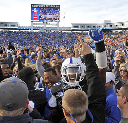Kentucky fans swarm onto the field, joining the players as they celebrate the end of a 26-game losing streak to Tennessee.  (AP)