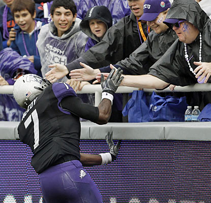 Horned Frog Greg McCoy leaps to the fans following his 99-yard kickoff return for a TD in the second quarter. (AP)