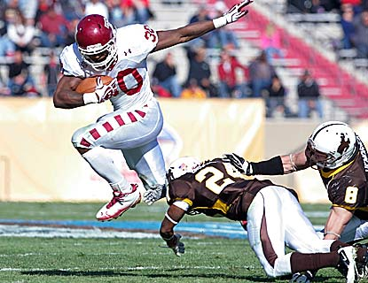 Bernard Pierce, leaping over two Cowboys, runs for two quick touchdowns as Temple wins its second bowl game in school history. (AP)