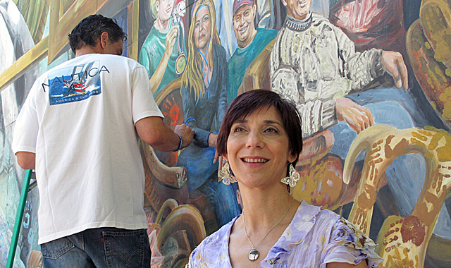 Ann Van Kuren, one of the 12 jurors who convicted Jerry Sandusky, poses next to the mural. (AP)