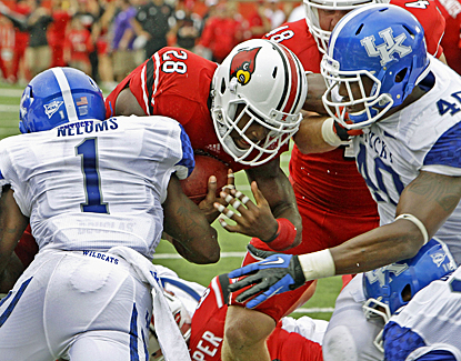 Louisville's Jeremy Wright (28) muscles through Kentucky's defense for three touchdowns. (AP)