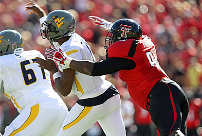 Geno Smith throws under pressure from Texas Tech's Kerry Hyder. Smith throws for 275 yards, but just one touchdown.   (AP)