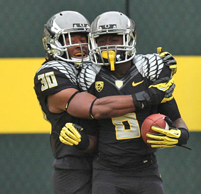 Ayele Forde helps De'Anthony Thomas celebrate after his electric 73-yard punt return for a touchdown  (US Presswire)